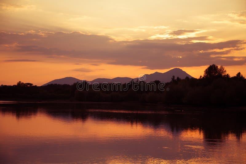 Um por do sol sobre as montanhas, um lago e uma floresta bonitos, coloridos em tons roxos Paisagem abstrata, brilhante fotos de stock
