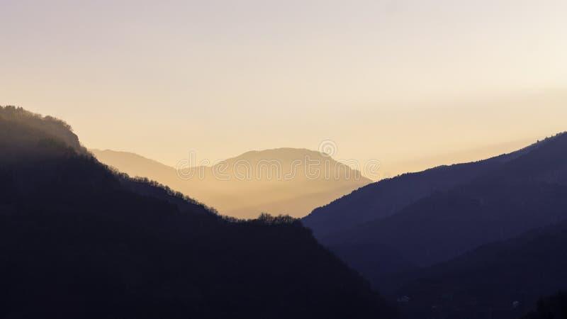 Um por do sol sobre montanhas e o céu claro imagens de stock