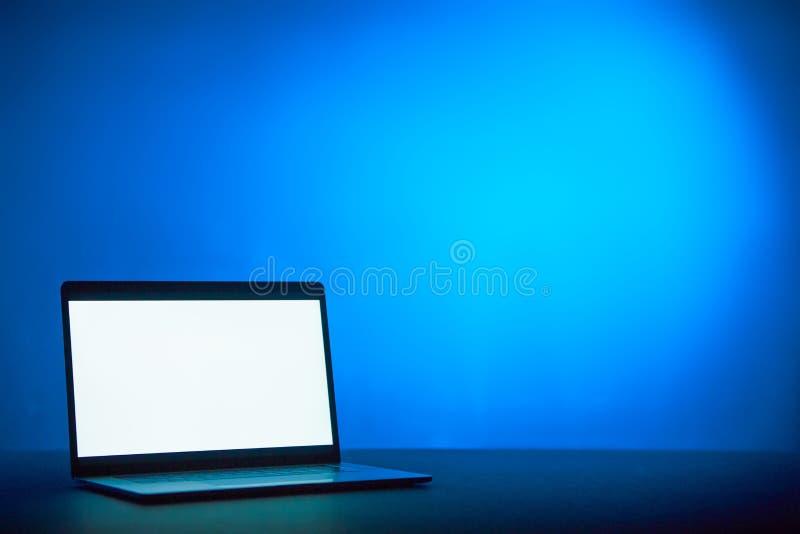 Um port?til com espa?o branco para o texto em um fundo est?tico azul fotografia de stock