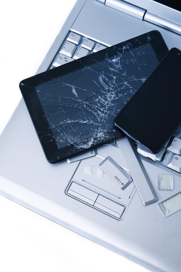Um portátil de prata com um teclado quebrado, a tabuleta com uma exposição rachada e o telefone preto Uma imagem do close-up da p fotografia de stock