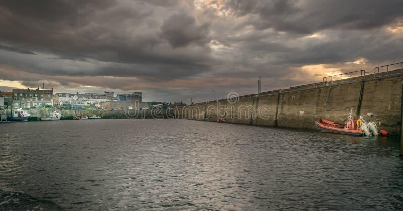 Um porto com os barcos vistos do mar com nuvens de tempestade foto de stock