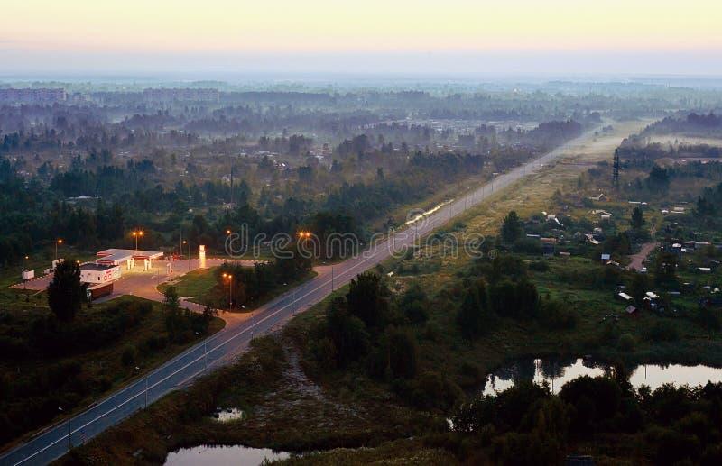 Um posto de gasolina e uma estrada direta no crepúsculo Vista de acima imagem de stock