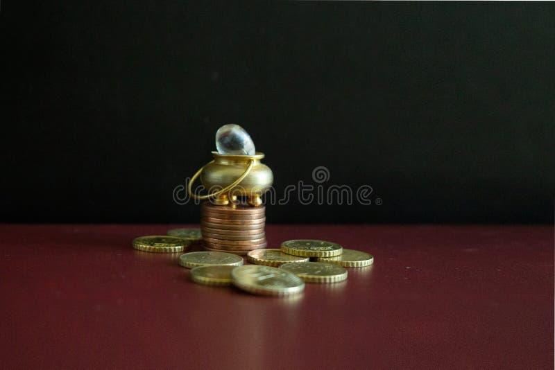 Um potenciômetro de ouro sobre algumas moedas empilhadas imagem de stock royalty free
