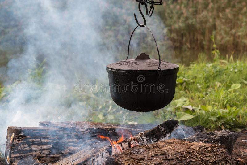 Um potenciômetro do alimento pendura sobre um fogo ardente foto de stock royalty free