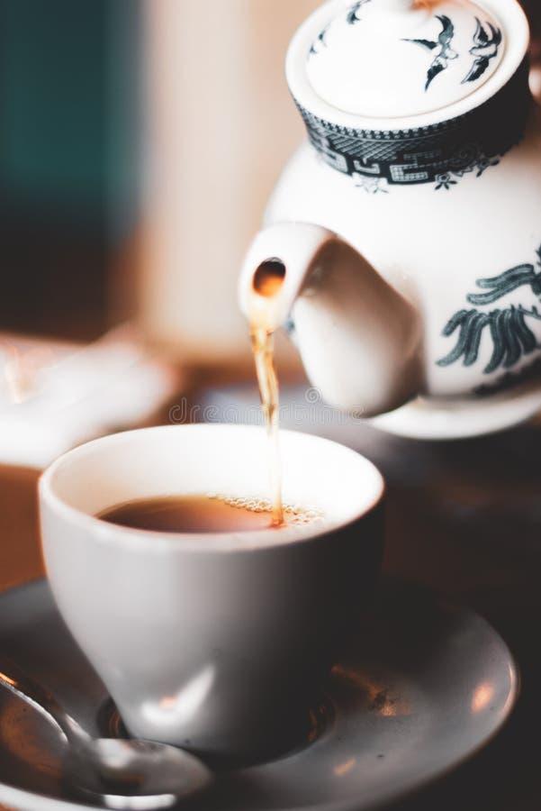 Um potenciômetro fresco do chá é derramado de um bule chinês em um copo e em uns pires imagem de stock