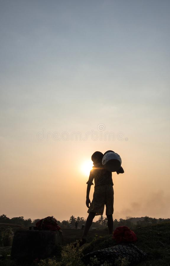Um potenciômetro levando da água da pessoa no tempo do por do sol, Mrauk U, Myanmar imagem de stock