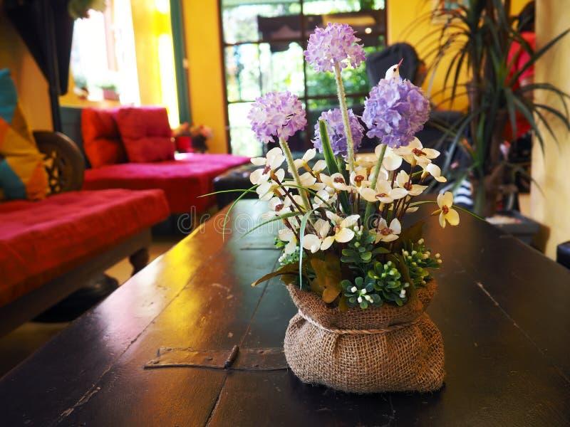 Um potenciômetro posto sobre a tabela de madeira na sala amarela A cor das flores é violeta, roxa, e branca com folhas verdes Sof imagens de stock
