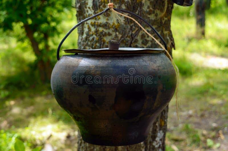 Um potenciômetro para cozinhar sobre um fogo aberto, pendurando na árvore Para caminhadas Estilo dos homens imagens de stock