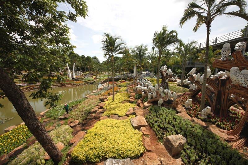 Um prado com coruja e grama e árvores e pedras e lagoa no jardim botânico tropical de Nong Nooch perto da cidade de Pattaya em Ta fotografia de stock royalty free