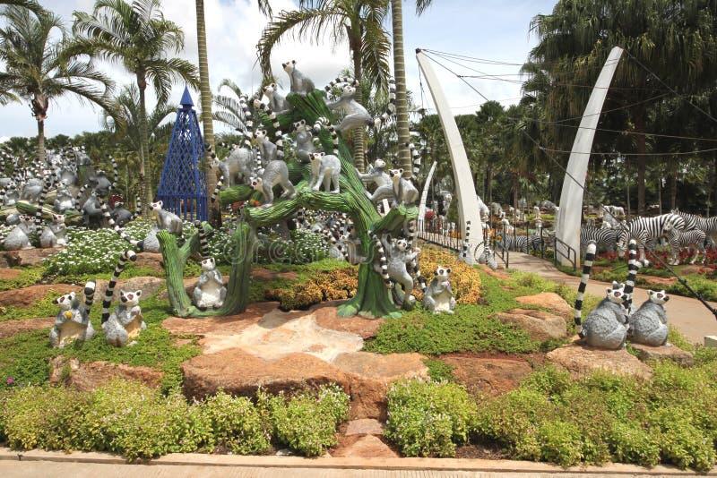 Um prado com guaxinins e grama e árvores e pedras no jardim botânico tropical de Nong Nooch perto da cidade de Pattaya em Tailând fotografia de stock
