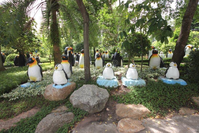 Um prado com pinguins e grama e árvores e pedras no jardim botânico tropical de Nong Nooch perto da cidade de Pattaya em Tailândi imagem de stock royalty free