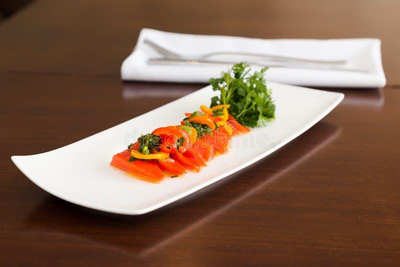 Um prato do crudo dos salmões de sockeye em uma placa branca com ervas frescas fotos de stock royalty free