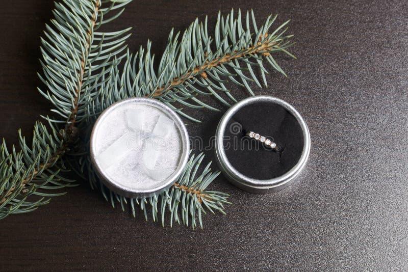Um presente a um amado Uma caixa de prata aberta com um anel de ouro Em um fundo escuro com um ramo spruce fotos de stock
