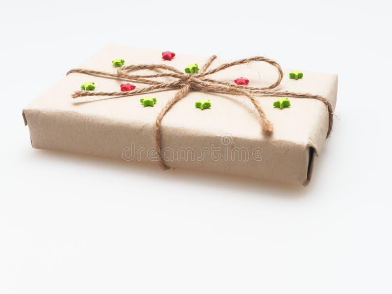 Um presente ou uma caixa de presente envolvido pelo marrom áspero reciclaram o papel e amarrams com corda marrom do cânhamo como  fotografia de stock royalty free