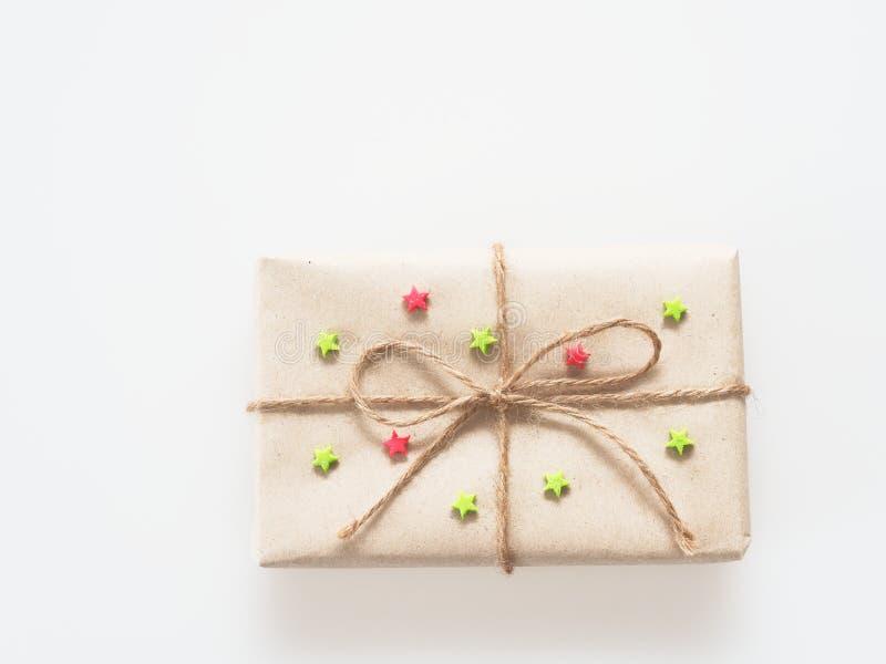 Um presente ou uma caixa de presente envolvido pelo marrom áspero reciclaram o papel e amarrams com corda marrom do cânhamo como  fotos de stock
