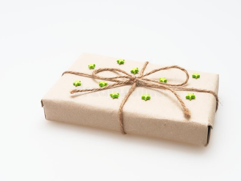 Um presente ou uma caixa de presente envolvido pelo marrom áspero reciclaram o papel e amarrams com corda marrom do cânhamo como  foto de stock