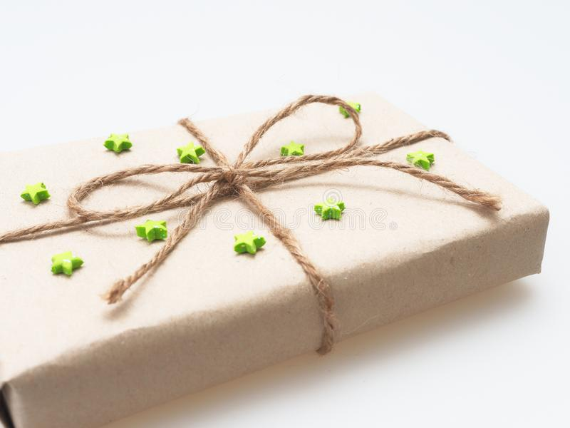 Um presente ou uma caixa de presente envolvido pelo marrom áspero reciclaram o papel e amarrams com corda marrom do cânhamo como  foto de stock royalty free