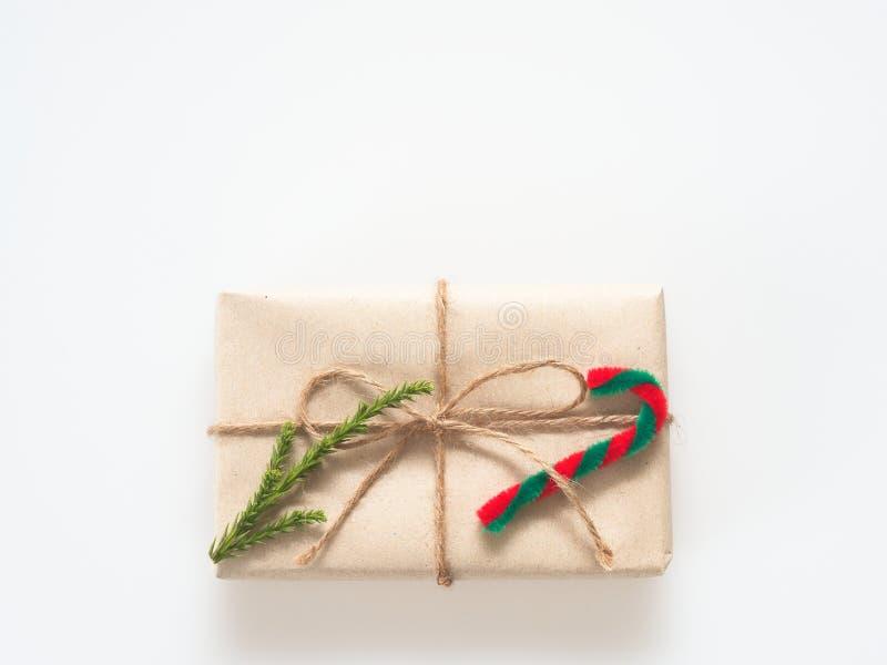 Um presente ou uma caixa de presente envolvido pelo marrom áspero reciclaram o papel e amarrams com a fita marrom da corda do cân imagens de stock