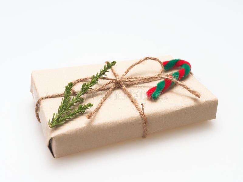 Um presente ou uma caixa de presente envolvido pelo marrom áspero reciclaram o papel e amarrams com a fita marrom da corda do cân imagem de stock