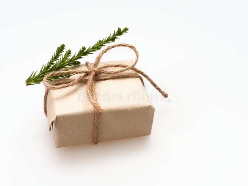 Um presente ou uma caixa de presente envolvido pelo marrom áspero reciclaram o papel e amarrams com a fita marrom da corda do cân fotografia de stock