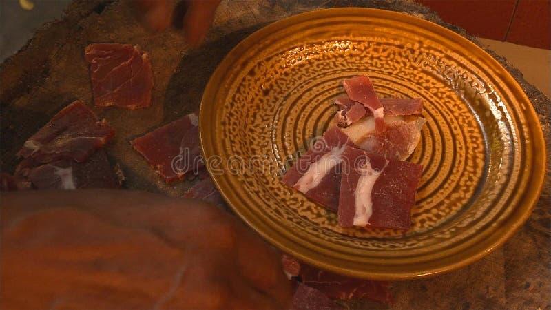 Um presunto maduro de Nuodeng será cortado em partes antes de cozinhar Alimento do chinês tradicional imagens de stock