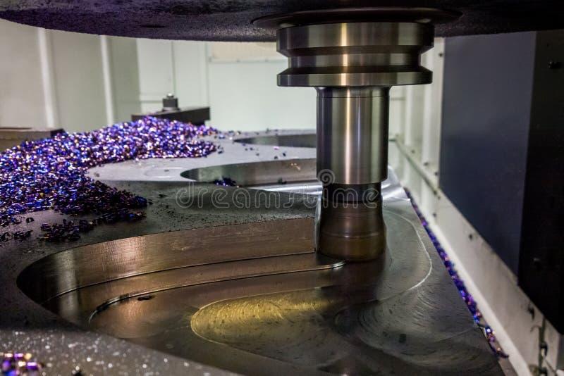 Um processo de trituração do cnc do palte de aço grosso do lagre pela trajetória curvada, foco seletivo com técnica do borrão fotografia de stock