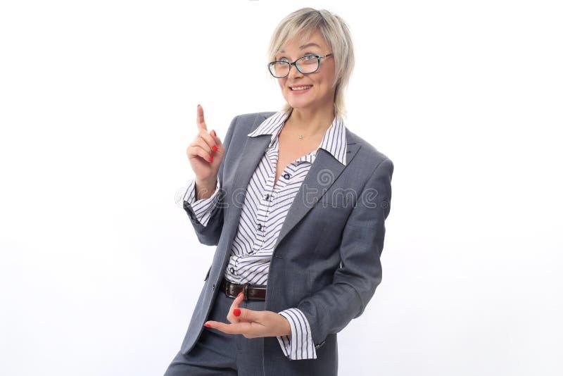 Um professor de meia idade, 40 anos idosos, em uma camisa listrada branca, em um terno cinzento e em uns vidros, com um tratament fotografia de stock