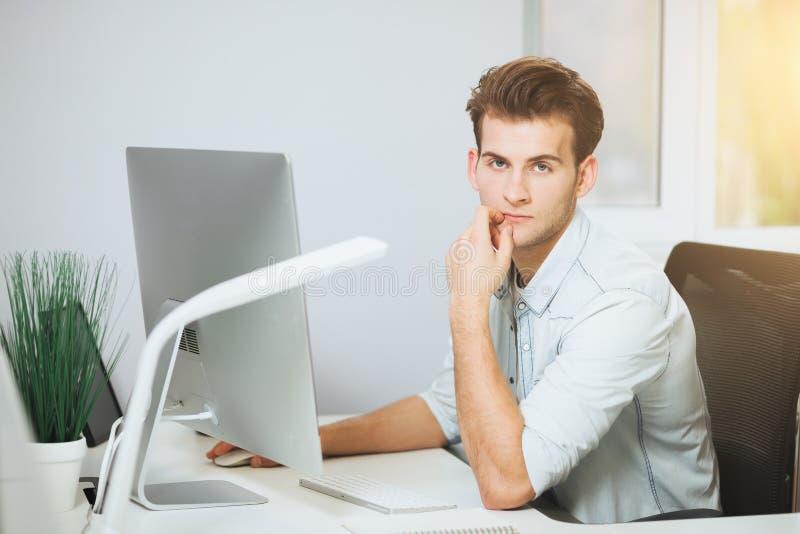 Um programador novo está olhando a câmera O designer gráfico está pensando sobre os projetos futuros O indivíduo novo imagem de stock