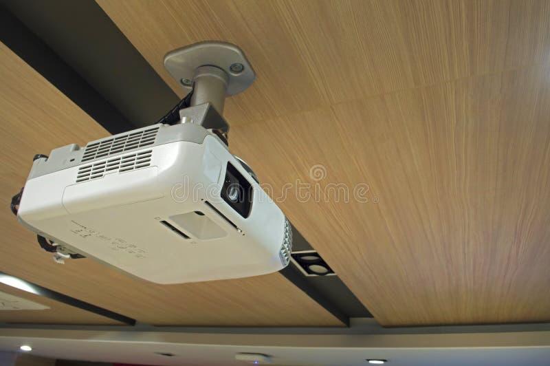 Um projetor aéreo branco no teto de madeira na sala de reunião foto de stock