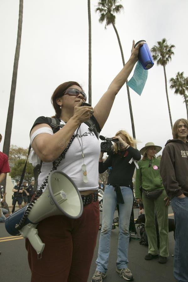 Um protestador da mulher com um orador alto gesticula com seu braço à multidão em uma marcha de protesto da guerra de anti-Iraque fotos de stock