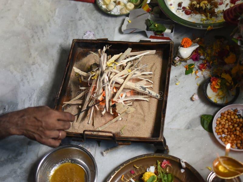 Um pujari ou um padre que arranjam a madeira na bandeja do fogo para o hom-joggo na adoração hindu fotografia de stock