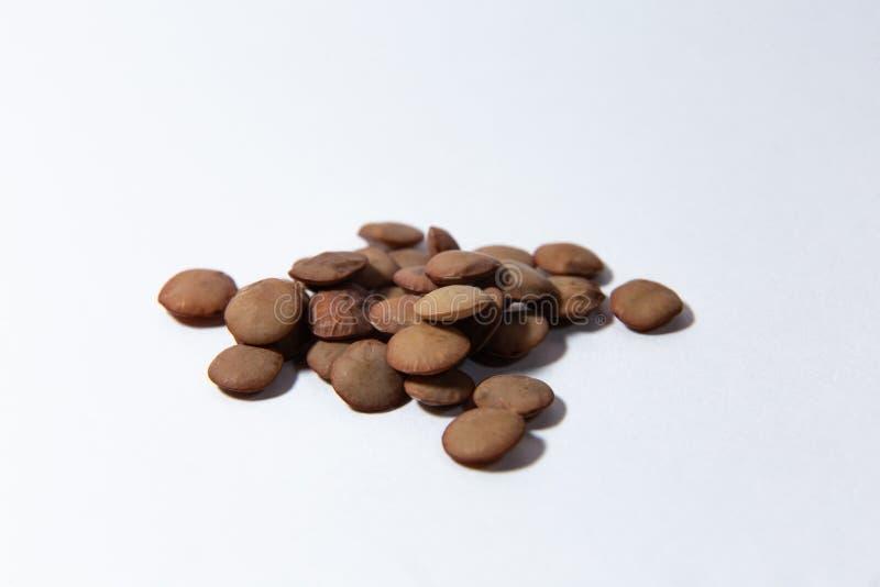 Um punhado das lentilhas encontra-se em um fundo branco fotografia de stock