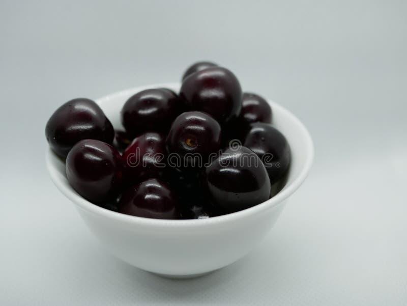 Um punhado de cerejas marrons maduras em uma bacia branca pequena da porcelana em um fundo branco vitamina natural da colheita da imagem de stock royalty free