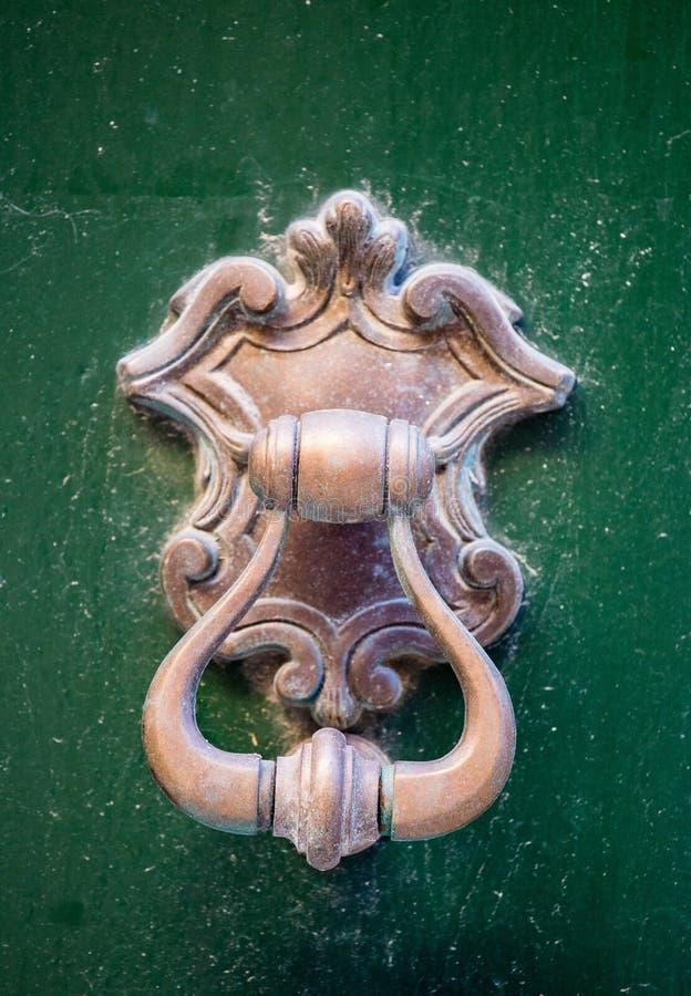 Um puxador da porta de bronze decorativo do estilo antigo em uma porta verde de madeira, na característica distintiva e no símbol imagens de stock