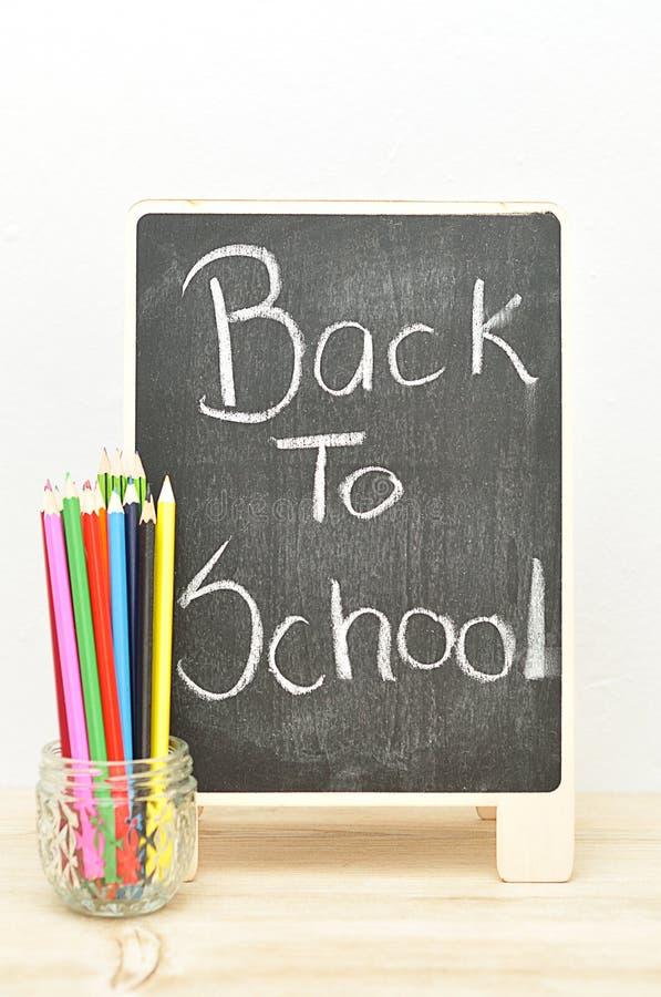 Um quadro-negro com as palavras de volta aos lápis da escola e da coloração imagem de stock