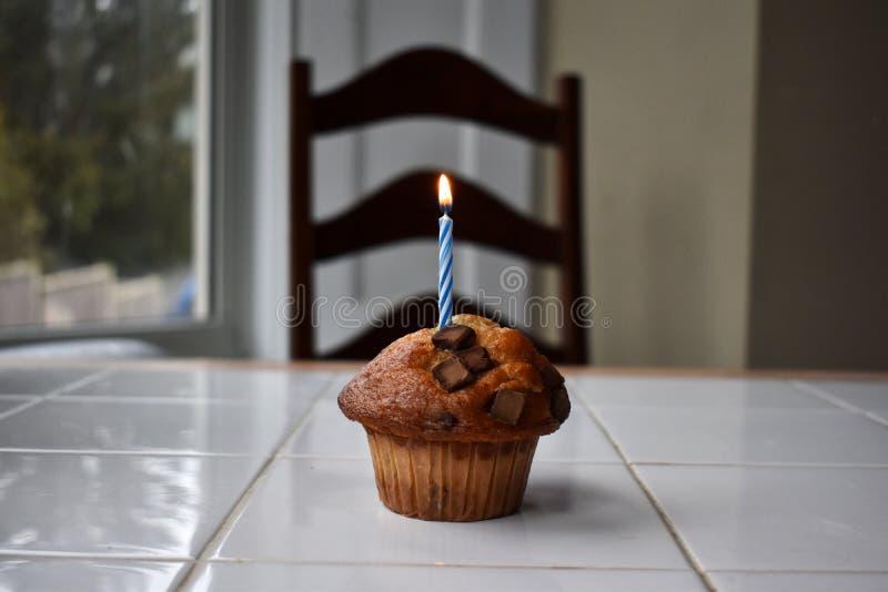 Um queque do aniversário com vela fotografia de stock