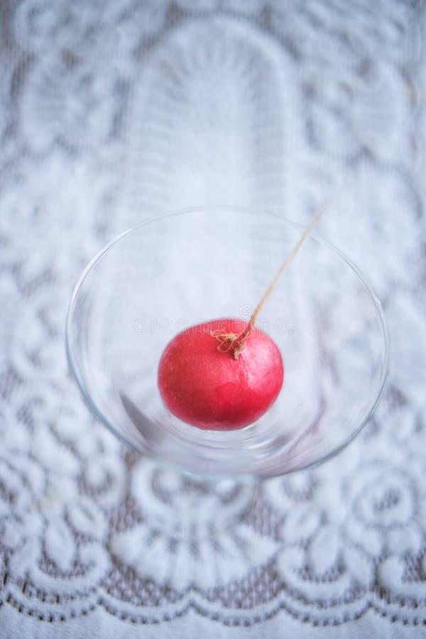 Um rabanete maduro em um vidro em uma toalha de mesa branca bonita imagem de stock