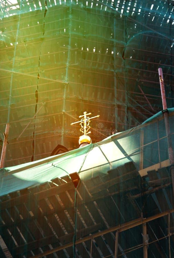 Um raio de luz na cruz de uma igreja ortodoxa durante o tempo de reparo imagem de stock