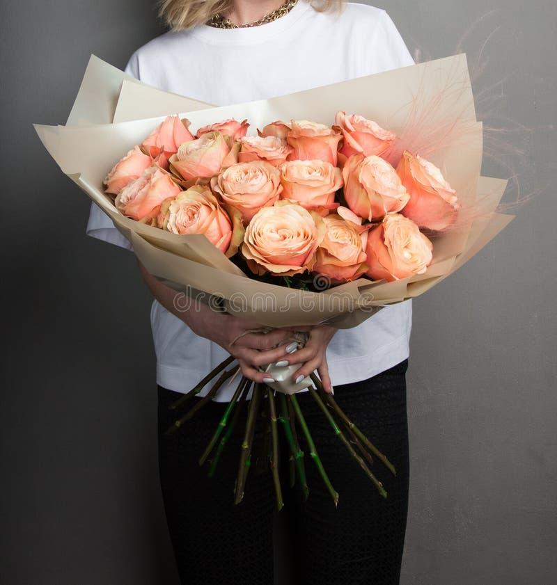 Um ramalhete bonito das flores das rosas, salm?es e cores alaranjadas, nas m?os de uma menina no papel do ouro fotografia de stock royalty free