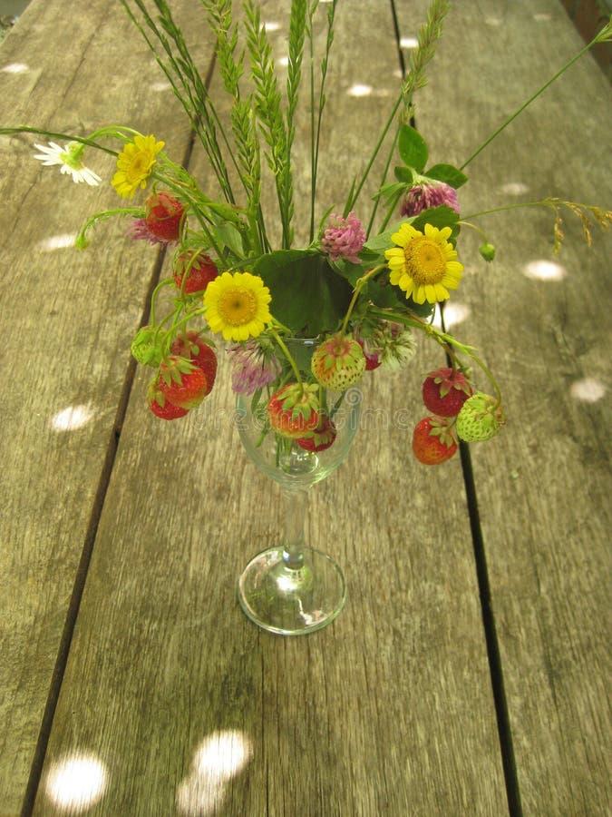 Um ramalhete da morango e flores selvagens e ervas em um vidro de vidro de vidro em uma tabela de carvalho longa imagem de stock royalty free