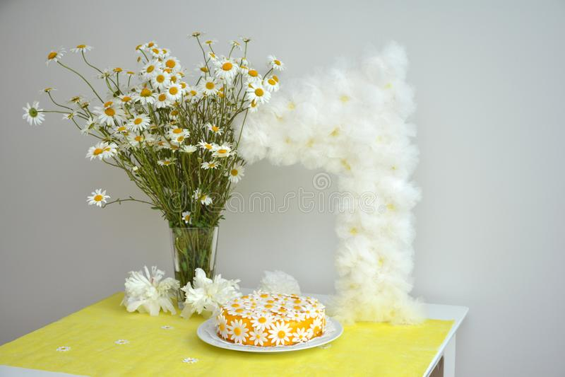 um ramalhete das camomilas e de um bolo de aniversário para meninas por 1 ano fotos de stock royalty free