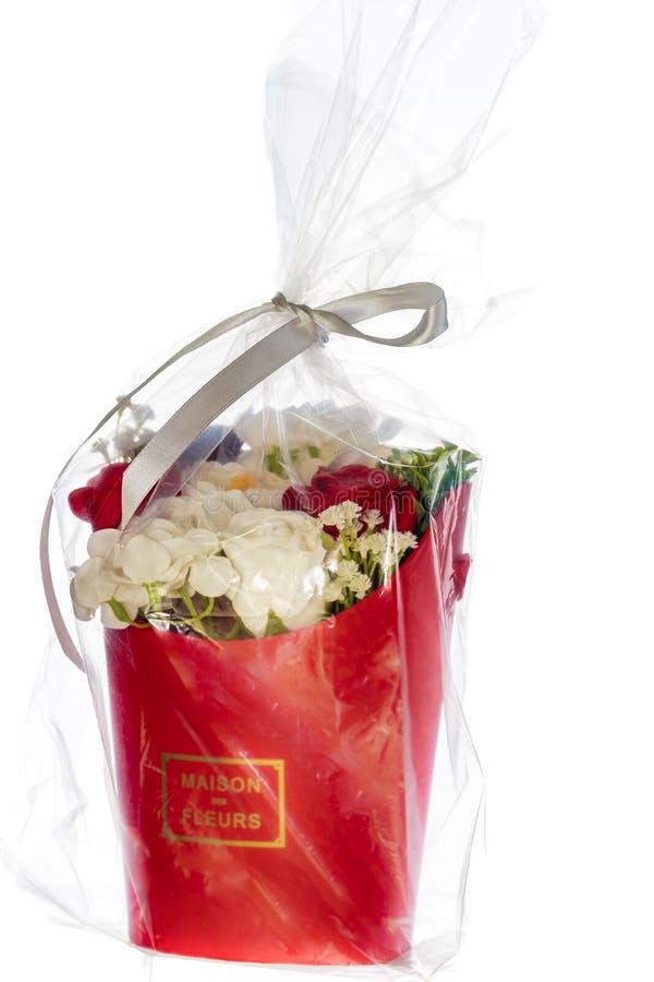 Um ramalhete das flores do sabão, de um vaso e de um brinquedo em um saco de empacotamento transparente fotos de stock