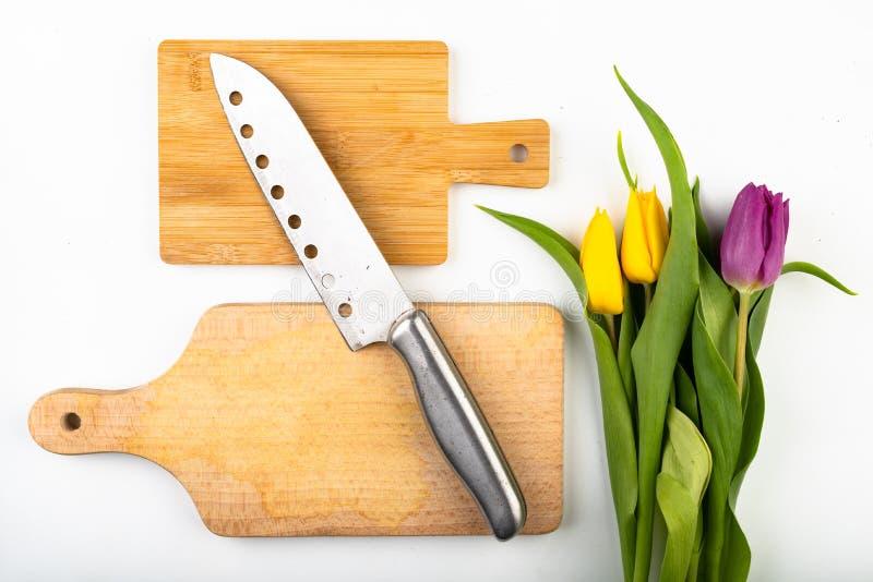 Um ramalhete das flores na mesa de cozinha Placa de desbastamento, faca e kvass de madeira foto de stock royalty free