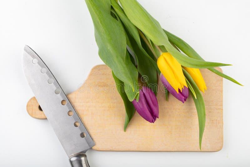Um ramalhete das flores na mesa de cozinha Placa de desbastamento, faca e kvass de madeira imagem de stock