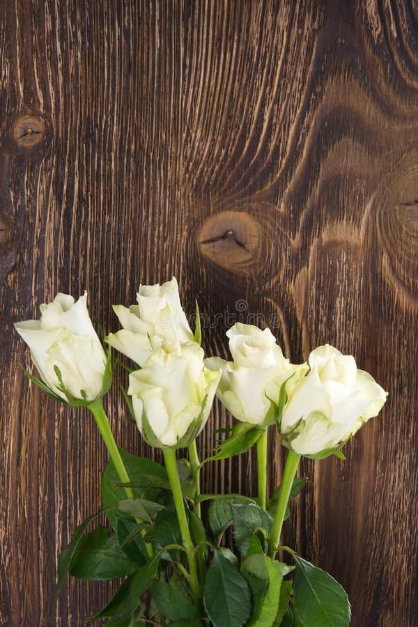 Um ramalhete das rosas brancas em um fundo de uma obscuridade de madeira fotos de stock