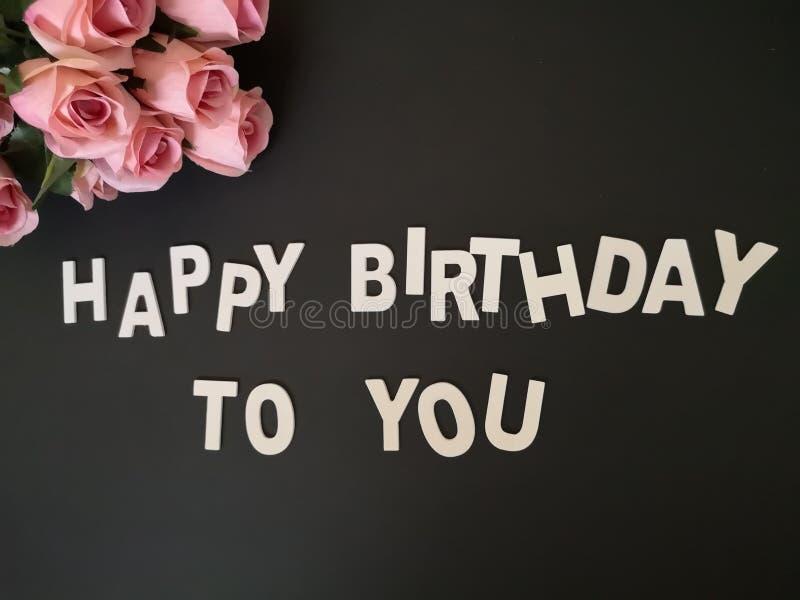 Um ramalhete das rosas que desejam um feliz aniversario com fundo preto fotografia de stock