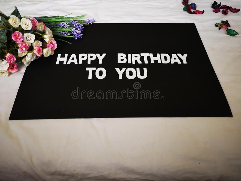 Um ramalhete das rosas que desejam um feliz aniversario com fundo preto foto de stock