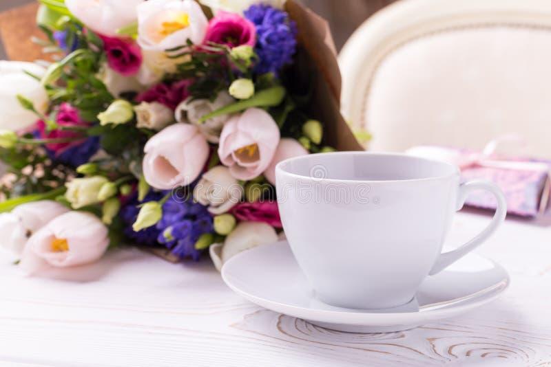 Um ramalhete das tulipas e de um copo branco em uma tabela de madeira branca Café da manhã maravilhoso da mola para o dia ou as m imagem de stock royalty free