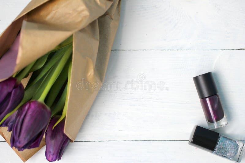 Um ramalhete das tulipas e do verniz para as unhas roxo: felicitações, o 8 de março dia internacional do ` s das mulheres, o 14 d imagens de stock