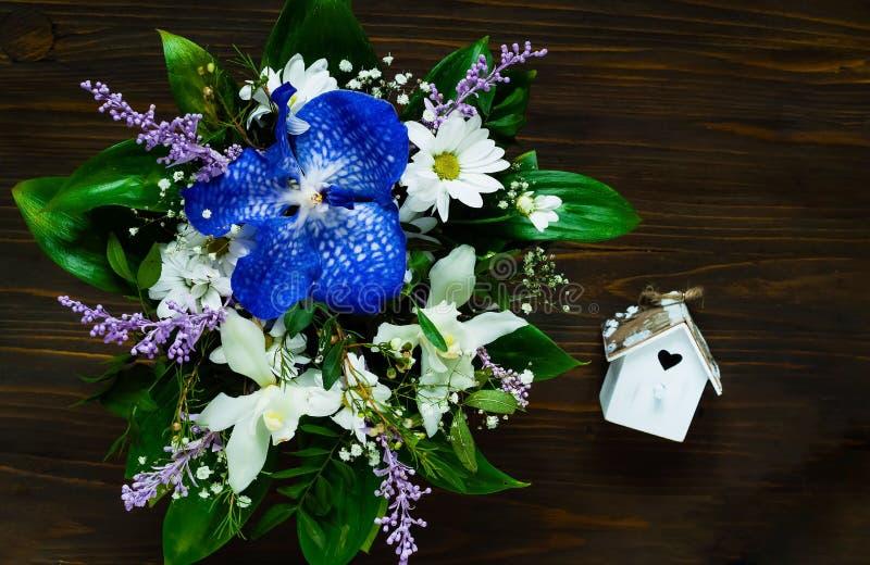 Um ramalhete de flores da mola e uma casa decorativa pequena com um coração em um fundo de madeira, um conceito da composição fes fotos de stock